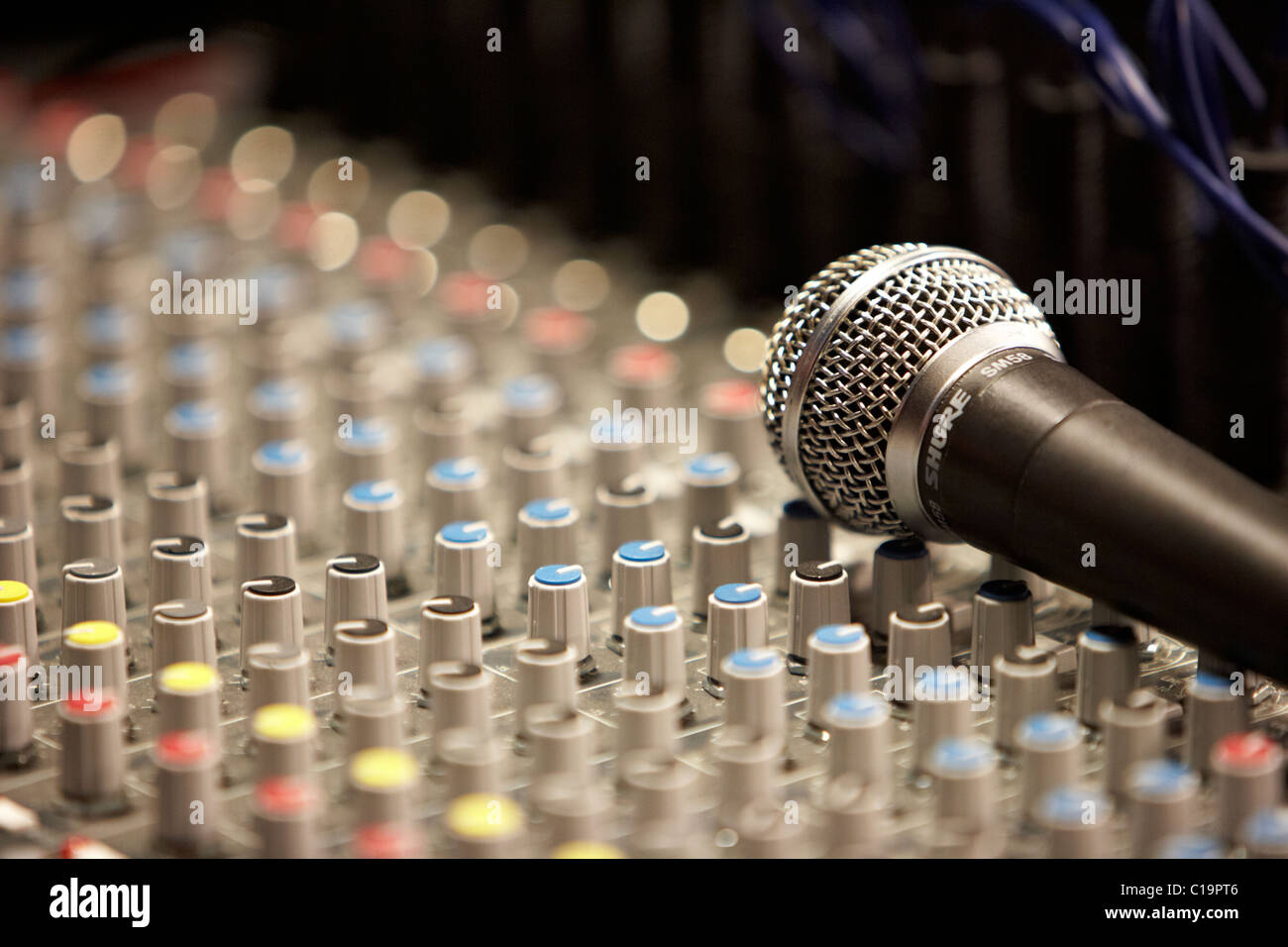 mic on an audio mixing desk in a theatre concert hall - Stock Image