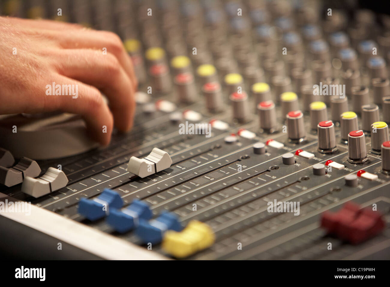 sliders and sound engineers hand on audio mixing desk in a theatre concert hall - Stock Image