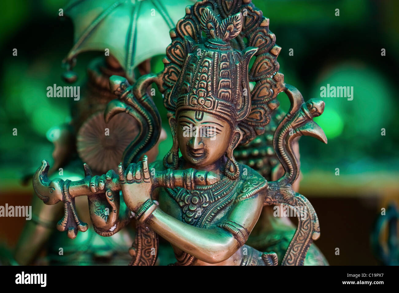 metallic statue of hindu god krishna playing the flute on shop display C19PX7