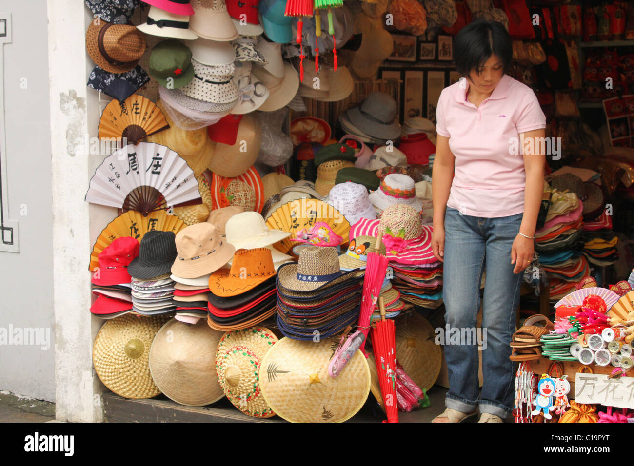 Chinese woman in a hat store. ZhouZhuang historic water town 8275ab69cdd1