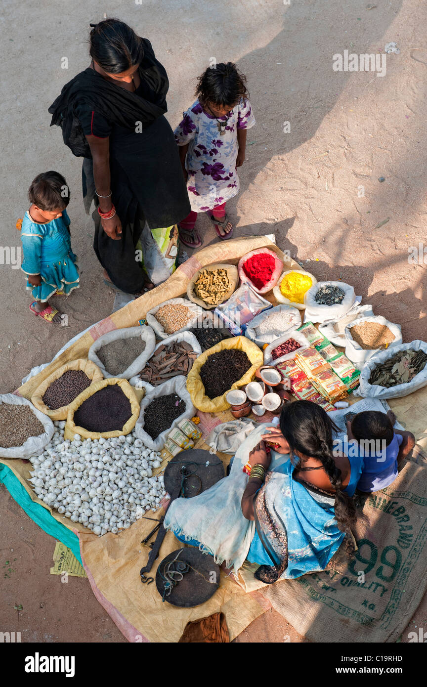 Indian family shopping at a street market with sacks of Indian spices and dried produce. Andhra Pradesh, India - Stock Image