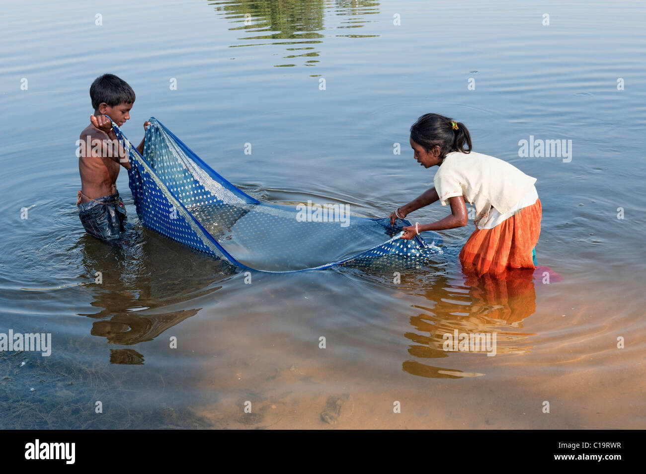 Poor Indian Lower Caste Children Catching Fish With A Sari In The