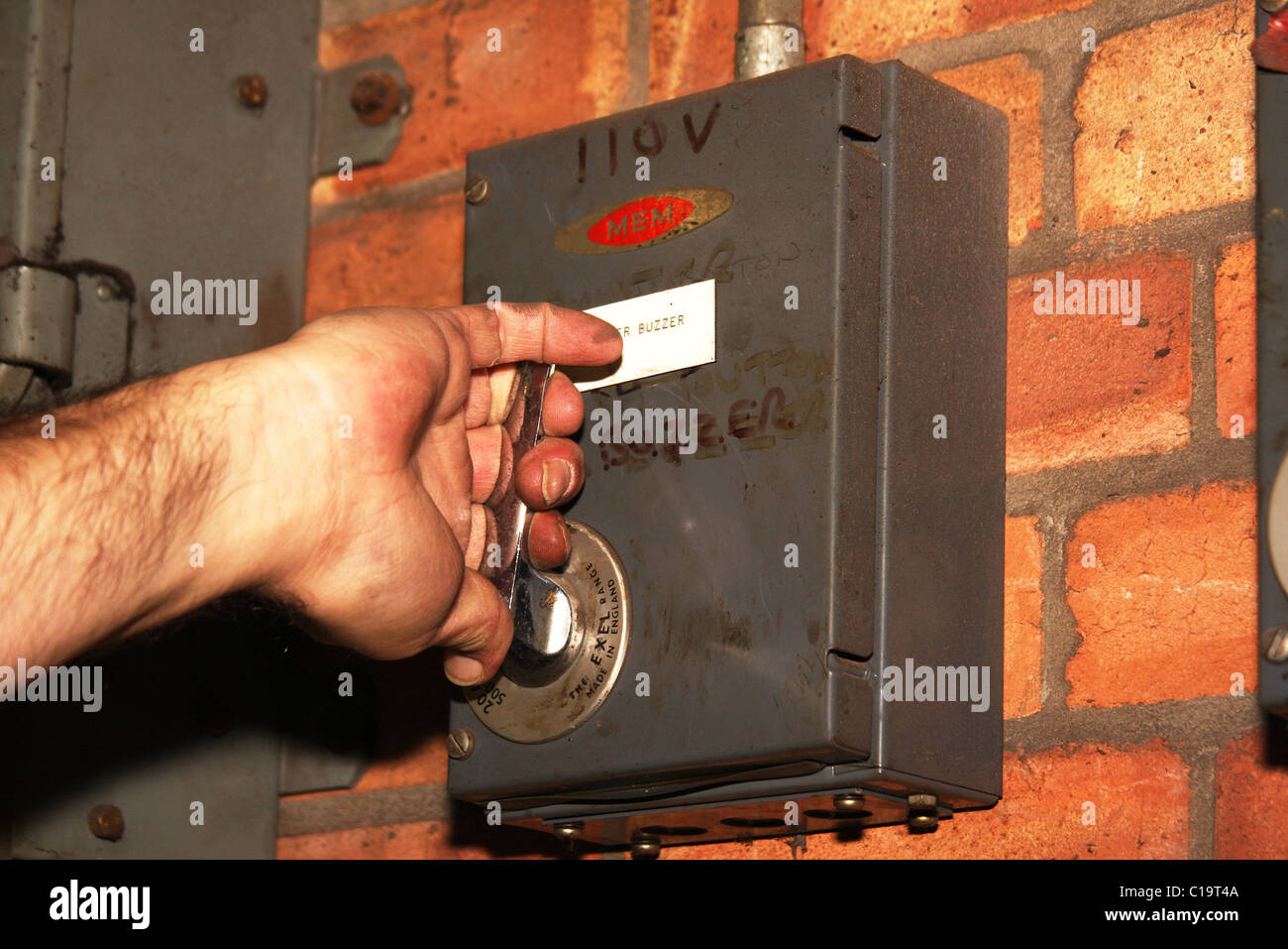 Hand about to operate 110 volt isolation switch. - Stock Image