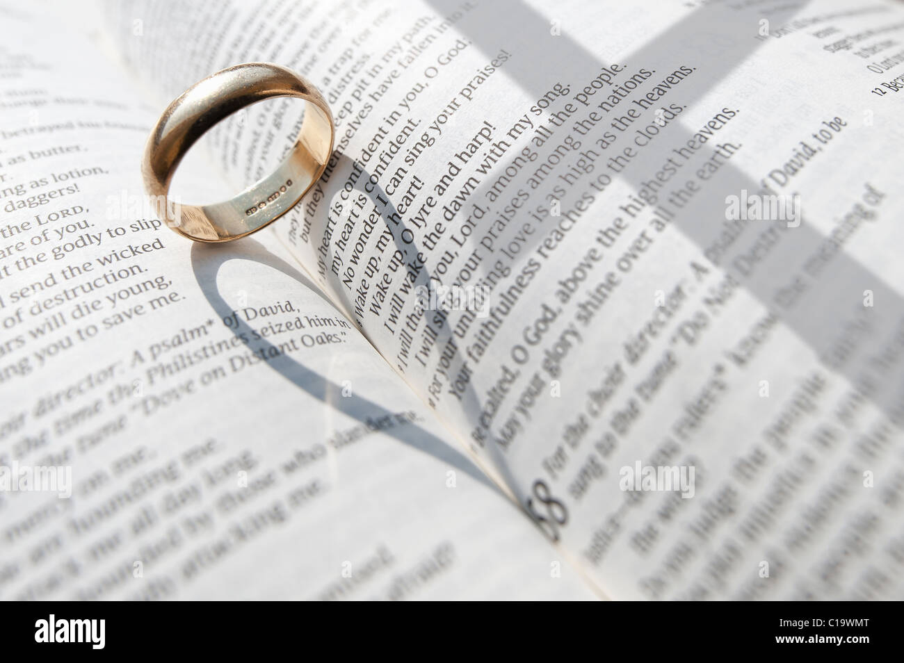 A wedding ring casting a shadow on the open pages of an open Stock