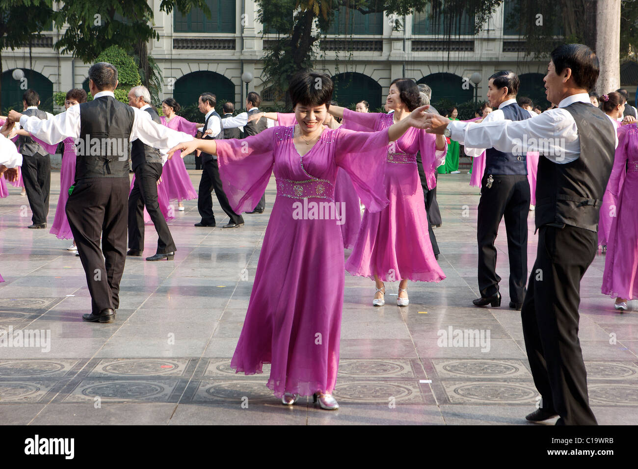 Colourful dancers early on a Sunday morning by Lake Hoan Kiem in the heart of Hanoi, Vietnam Stock Photo