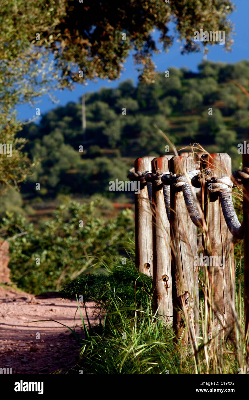 View of a dirt trail with a wooden fence with rope in the nature. - Stock Image