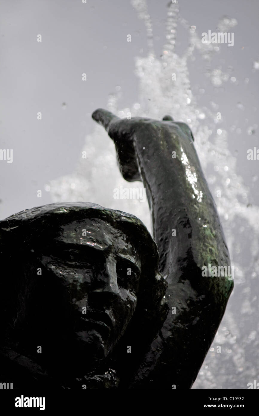 Closeup view of the female face of a iron statue with bursts of water behind. - Stock Image