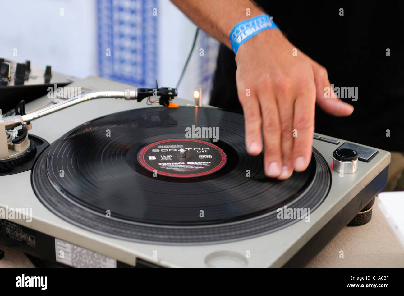 Dj Performing Live Mixing Music Using Mixer And Scratch
