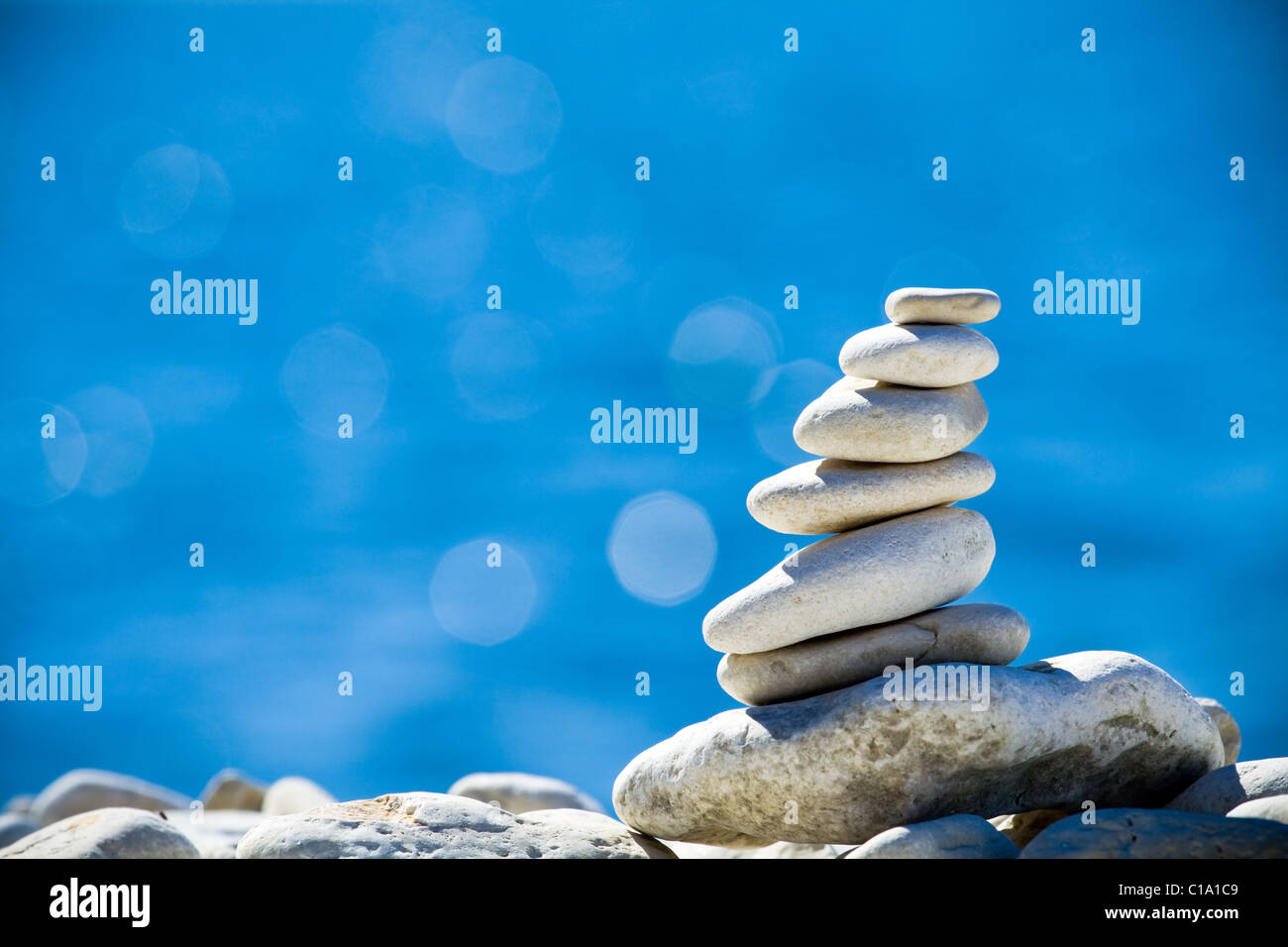 Close-up of white pebbles stack over blue sea - Stock Image