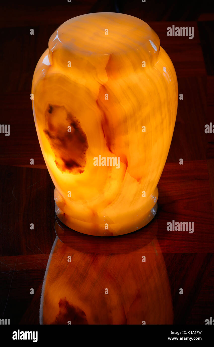 Onyx stone cremation urn glowing with an inside light on a wooden table - Stock Image