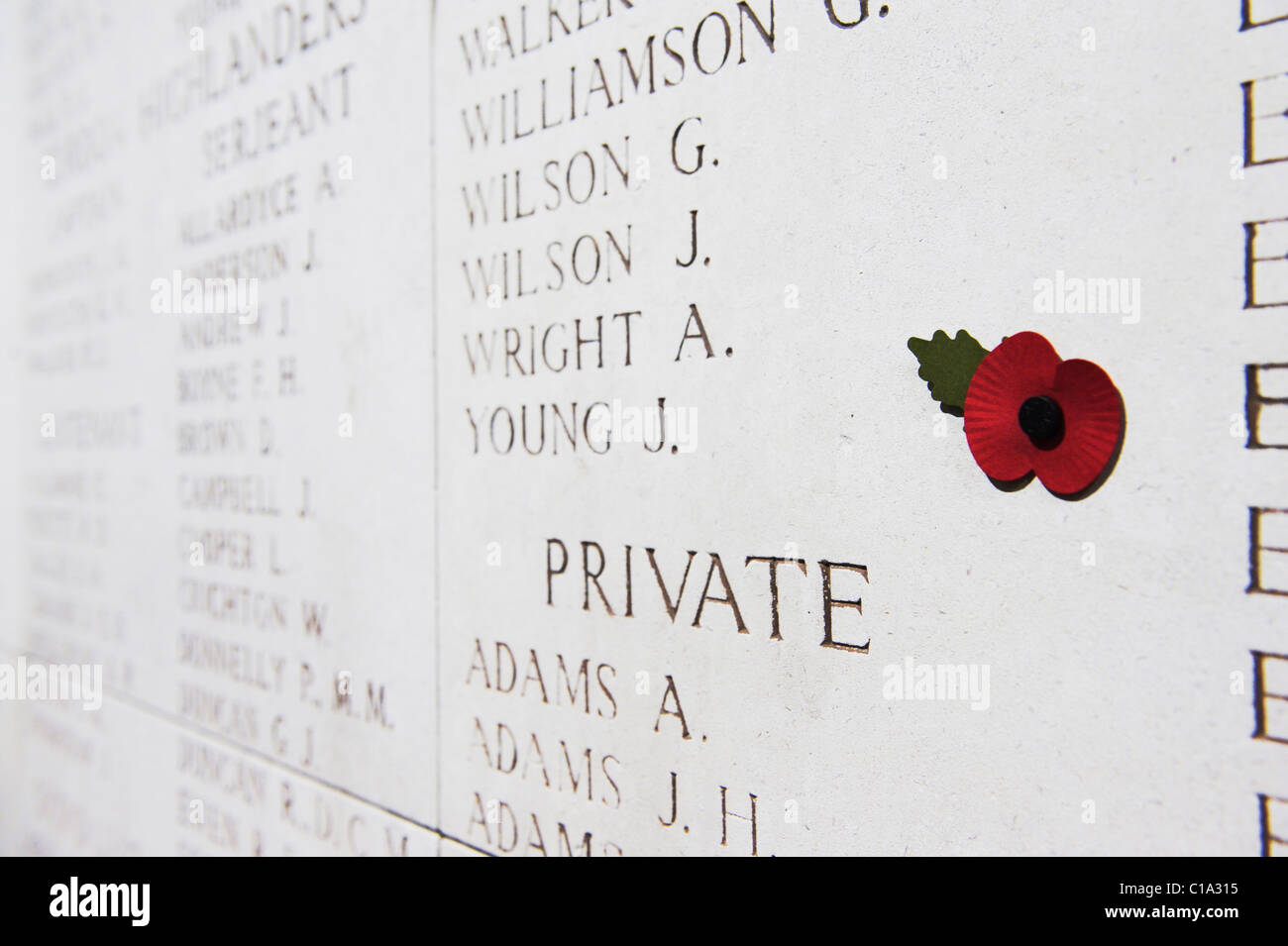 Menin Gate Memorial to the Missing, with a poppy in foreground - Stock Image