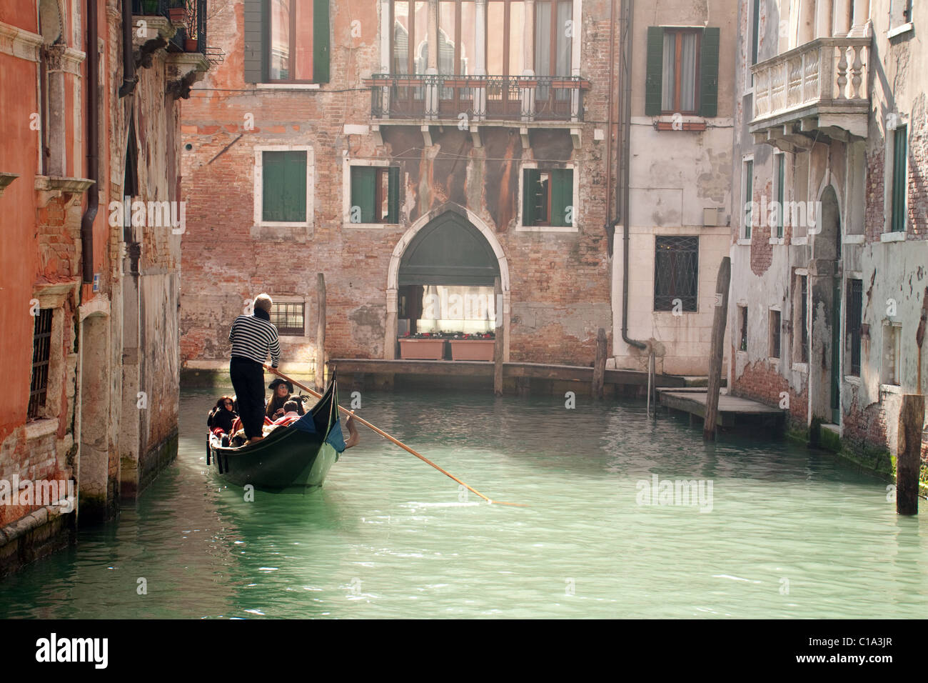 A gondolier guides his gondola along the narrow canals, Venice, Italy - Stock Image