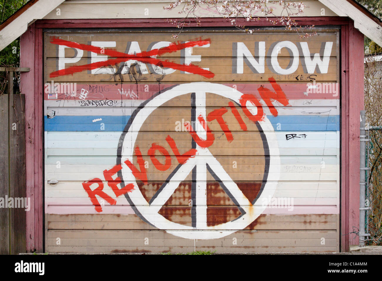 Peace and revolution sign graffiti painted on garage door-Victoria, British Columbia, Canada. - Stock Image