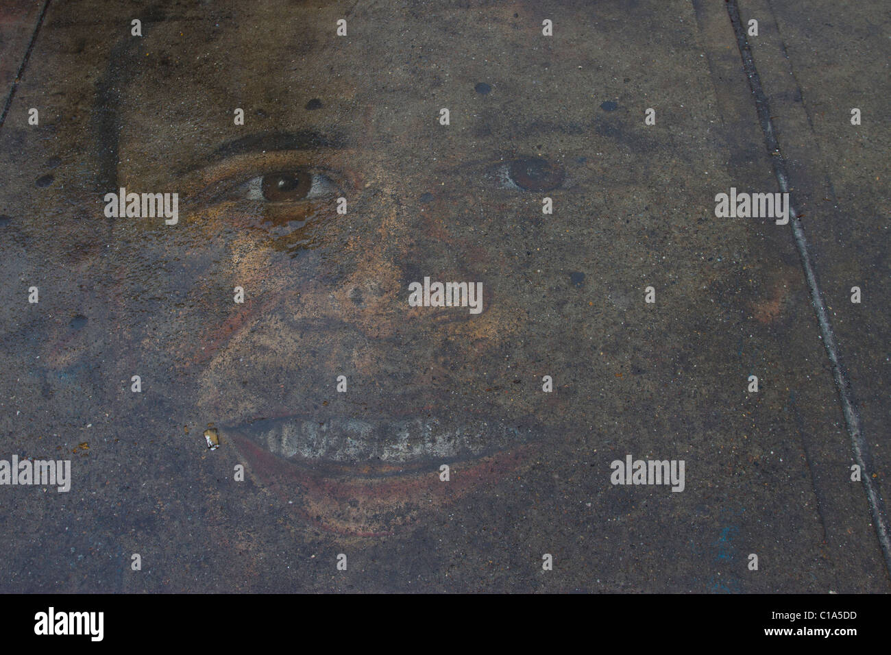 Street artist's fading rendering of Barack Obama on a sidewalk in Manhattan on a rainy day - Stock Image