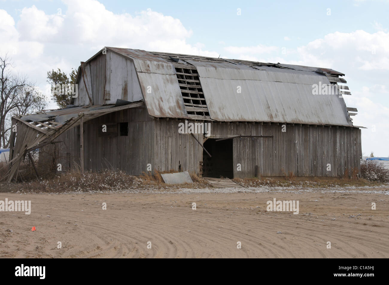 Photograph of an old barn in Arkansas needing repair, Sandy foreground with a blue sky and cotton modules in the - Stock Image