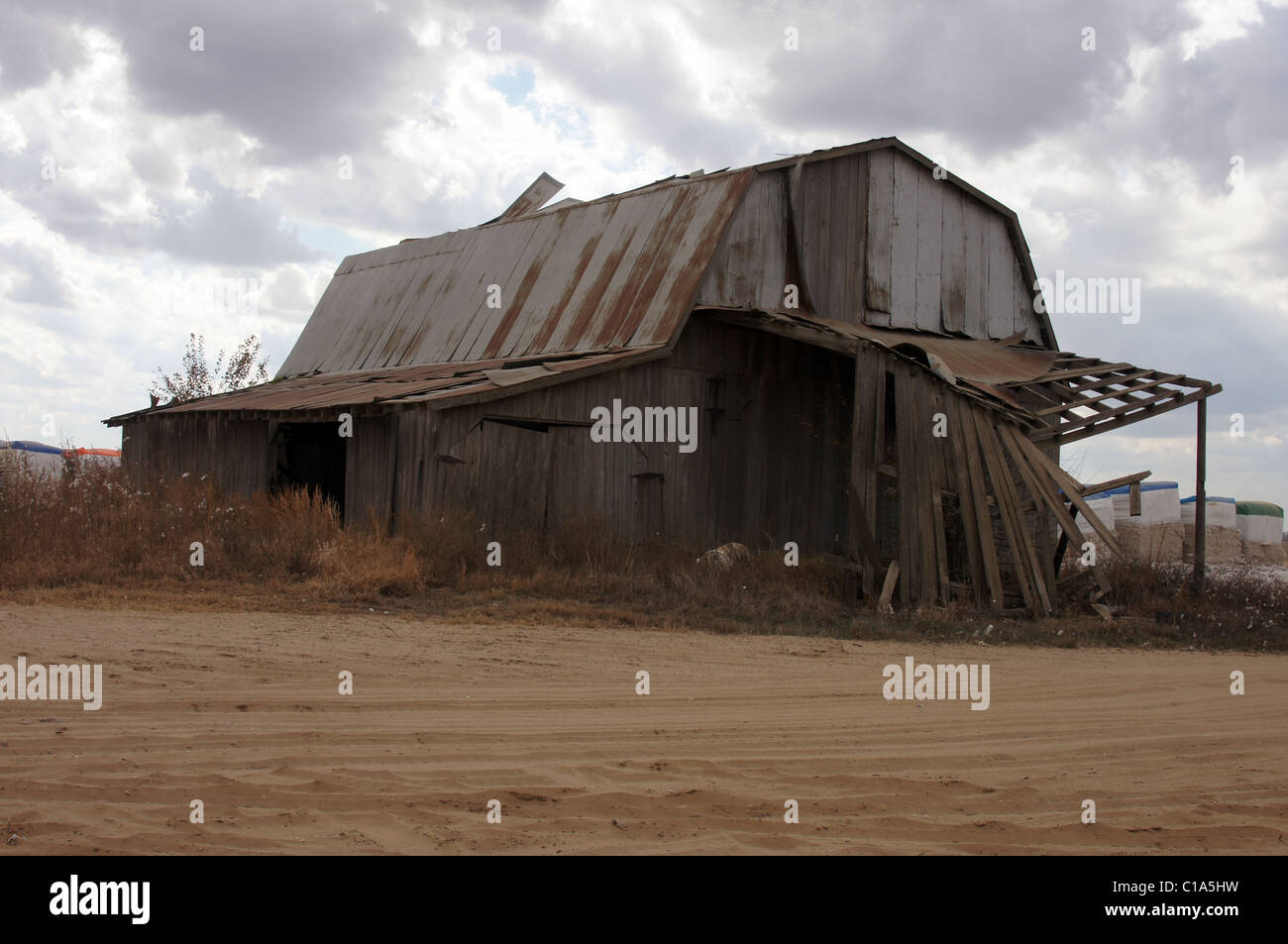 An old barn needing repair with sandy foreground and cotton modules waiting to be ginned in the background - Stock Image