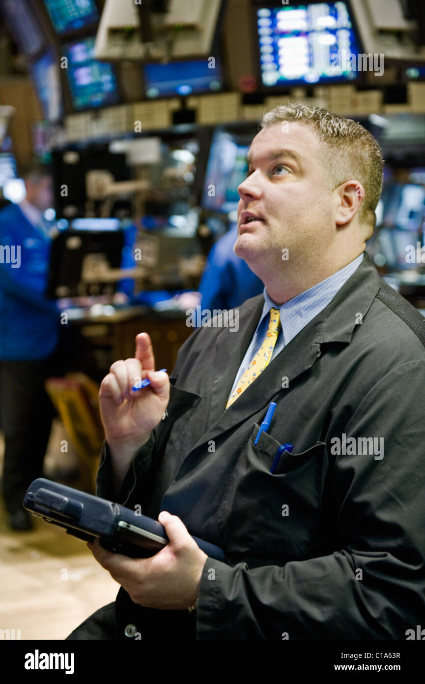 A Trader consults his hand-held terminal to figure out his next order. Stock Photo