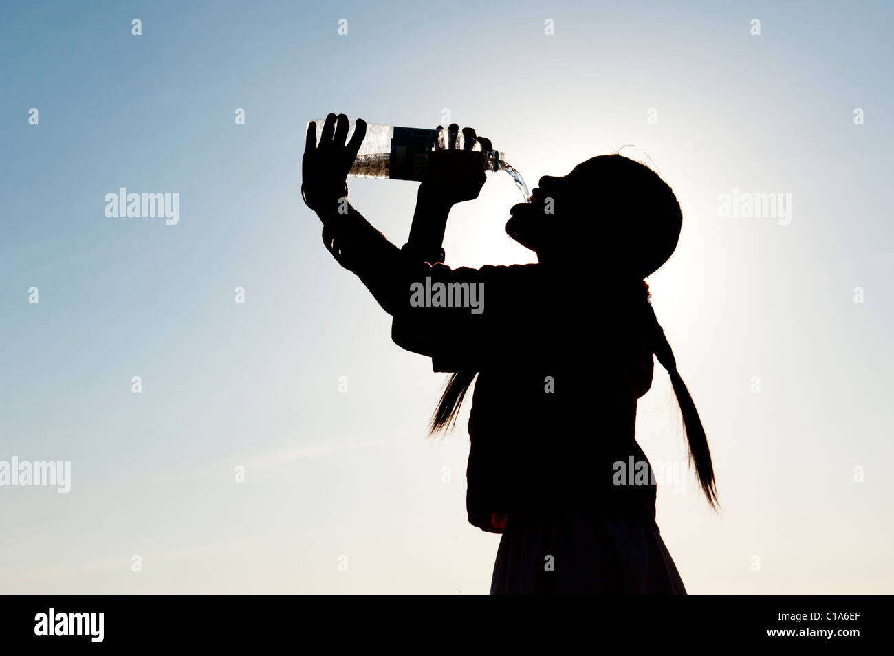 Indian girl drinking mineral water from plastic water bottle. India. Silhouette Stock Photo