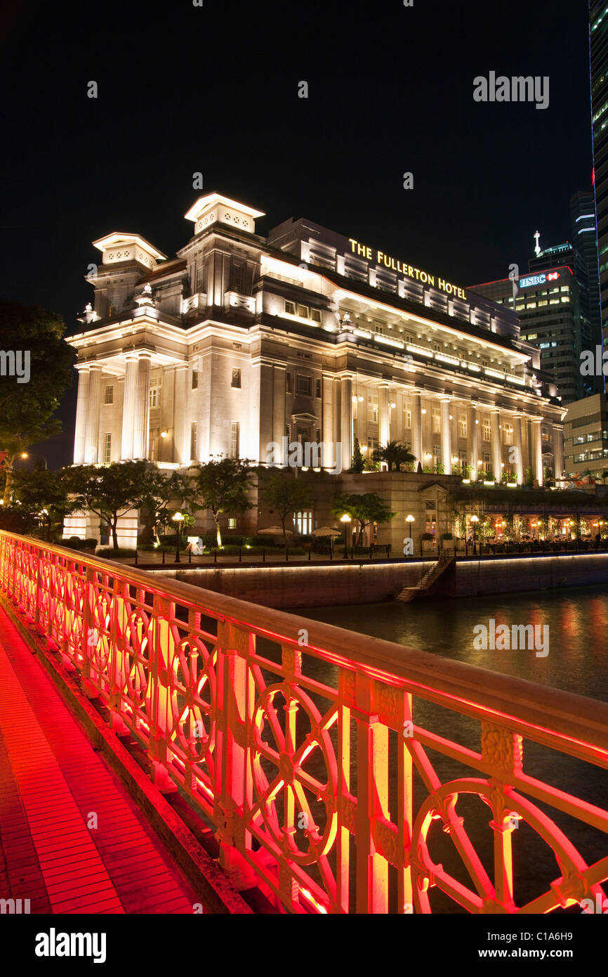 The Fullerton Hotel and Anderson Bridge illuminated at night, Singapore - Stock Image