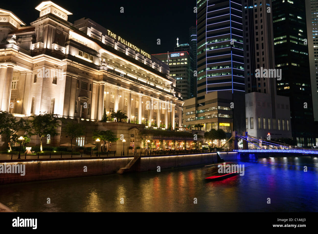 The Fullerton Hotel and Singapore River illuminated at night, Singapore - Stock Image