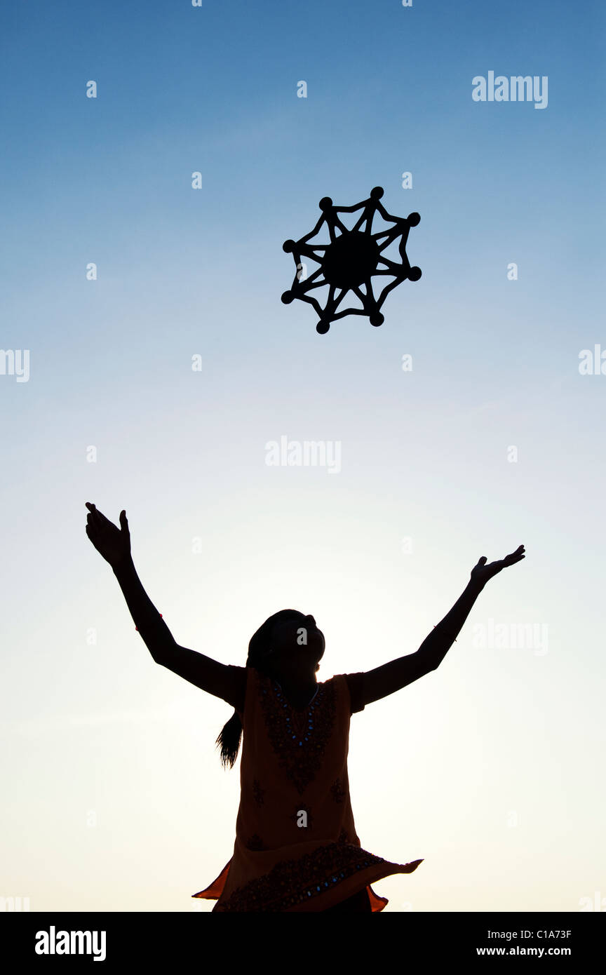 Silhouette indian girl throwing a symbol of one world, unity and humanity into the air. India - Stock Image