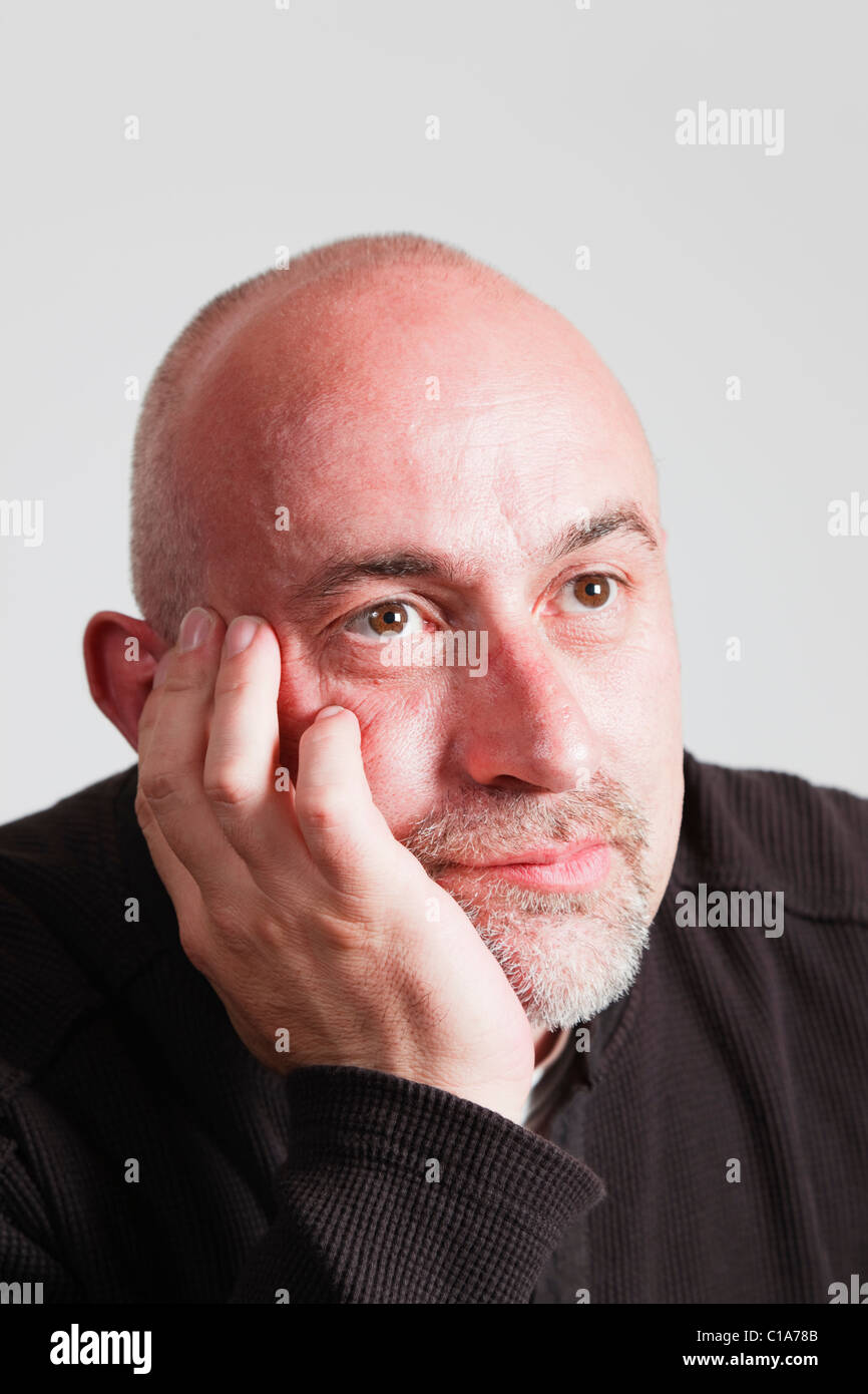 UK, Europe. Bald headed mature man resting his chin on his hand with a bored facial expression staring into the - Stock Image