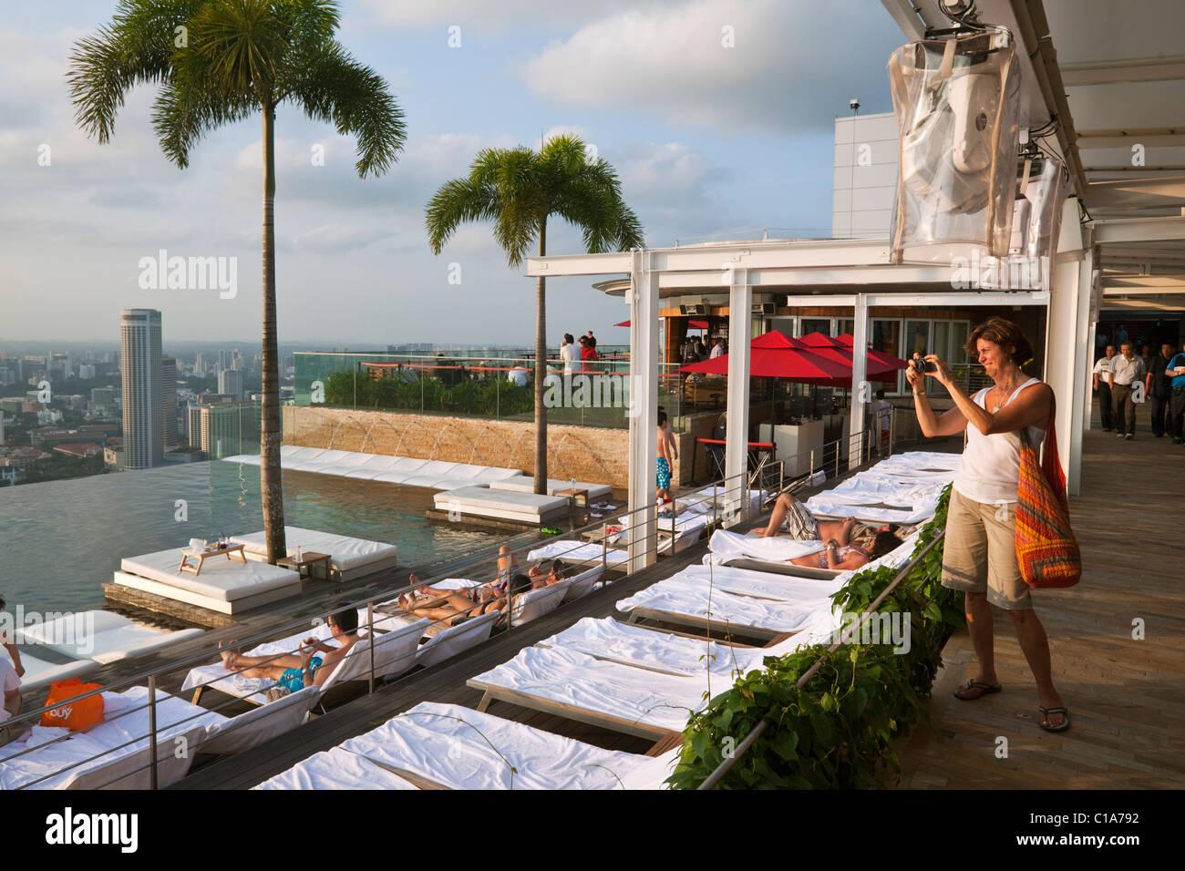 Woman photographing the swimming pool at the Marina Bay Sands SkyPark.  Marina Bay, Singapore - Stock Image