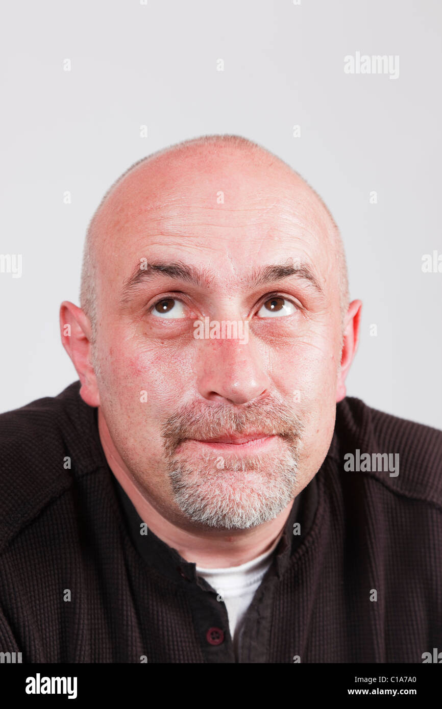Mature man looking upwards and thinking with a faraway facial expression and raised eyebrows. UK, Britain - Stock Image