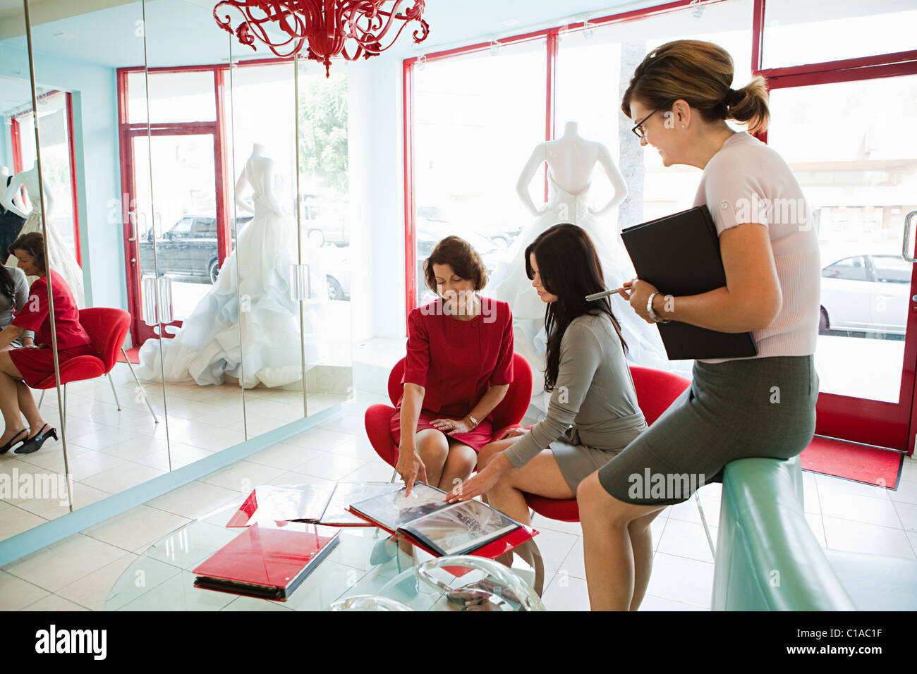 Mother and daughter talking to wedding dress designer - Stock Image