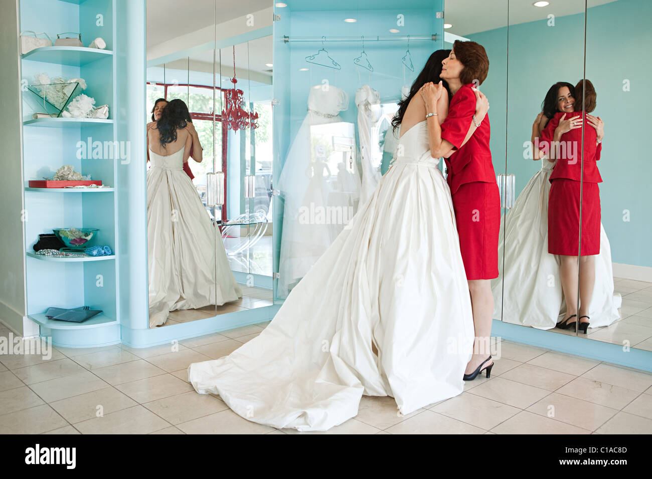 Daughter trying on wedding dress, embracing mother Stock Photo ...
