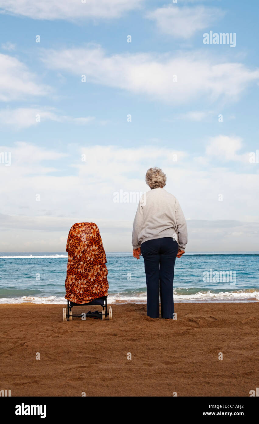 Elderly lady standing next to her shopping trolley on beach - Stock Image