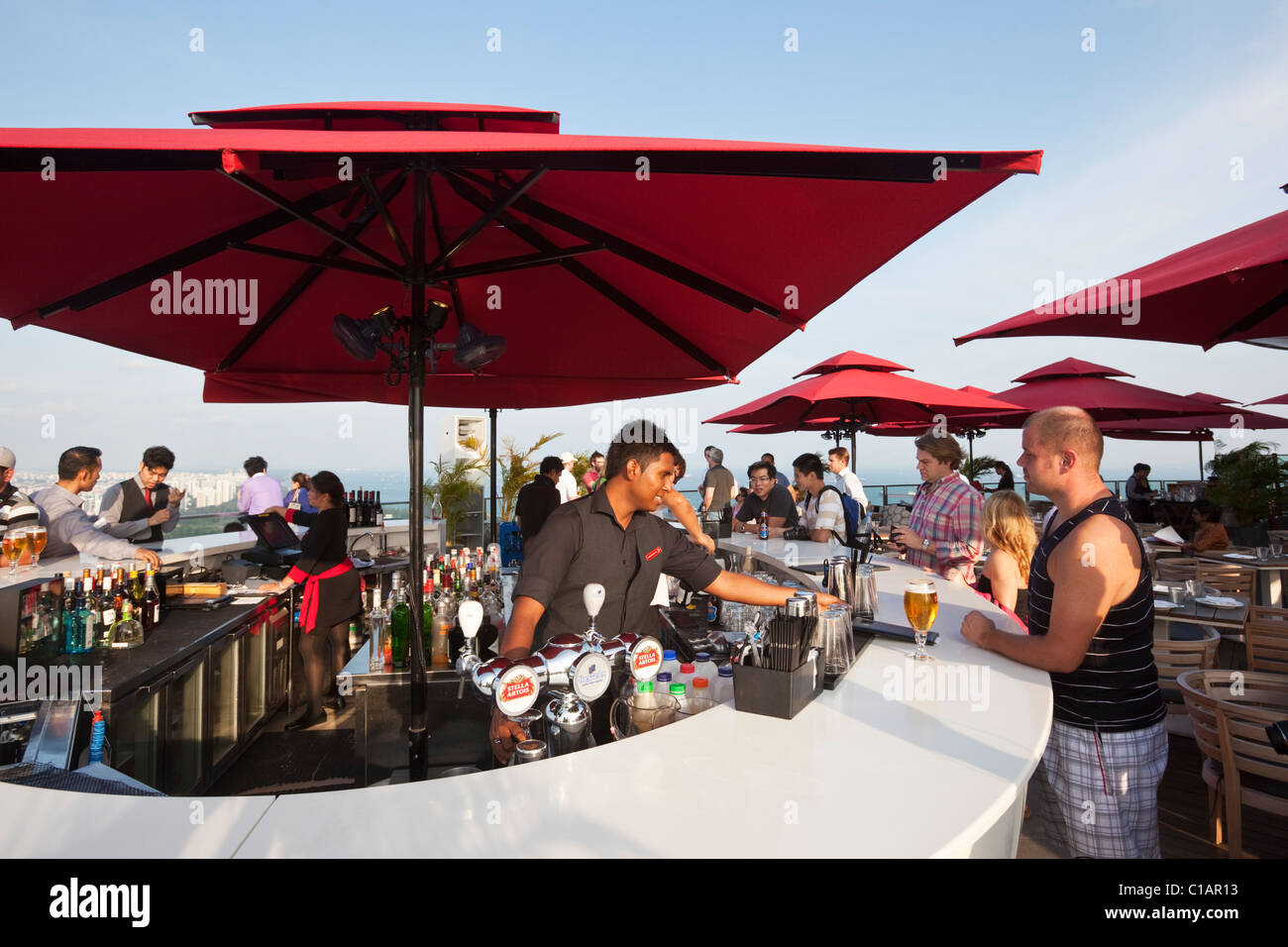 Sunset drinks at the rooftop bar of the Marina Bay Sands SkyPark - 200 metres above the city.  Marina Bay, Singapore - Stock Image