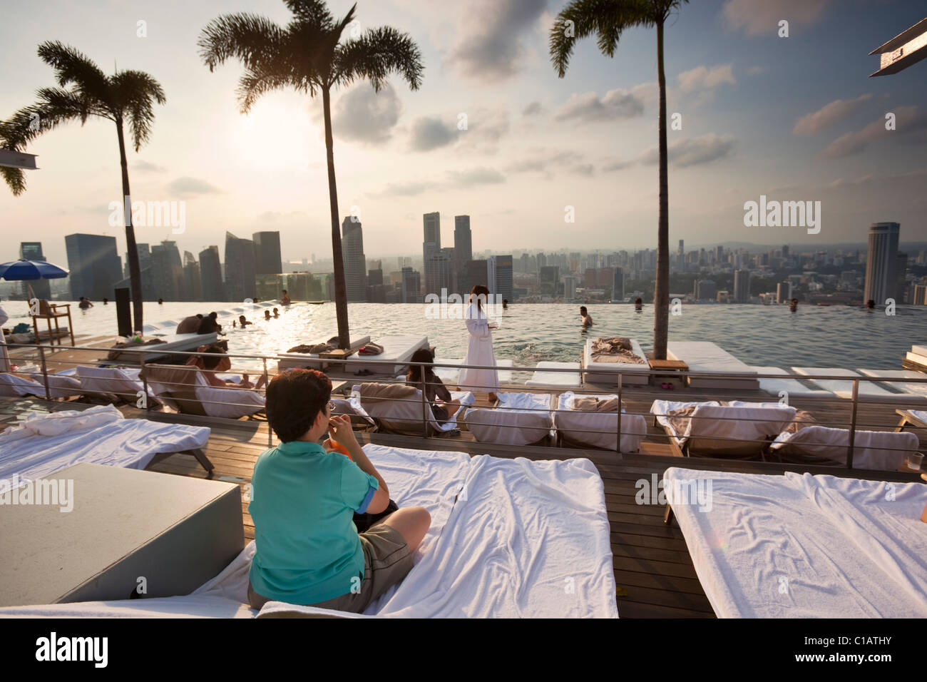 Woman drinking cocktails at the Marina Bay Sands SkyPark pool.  Marina Bay, Singapore - Stock Image