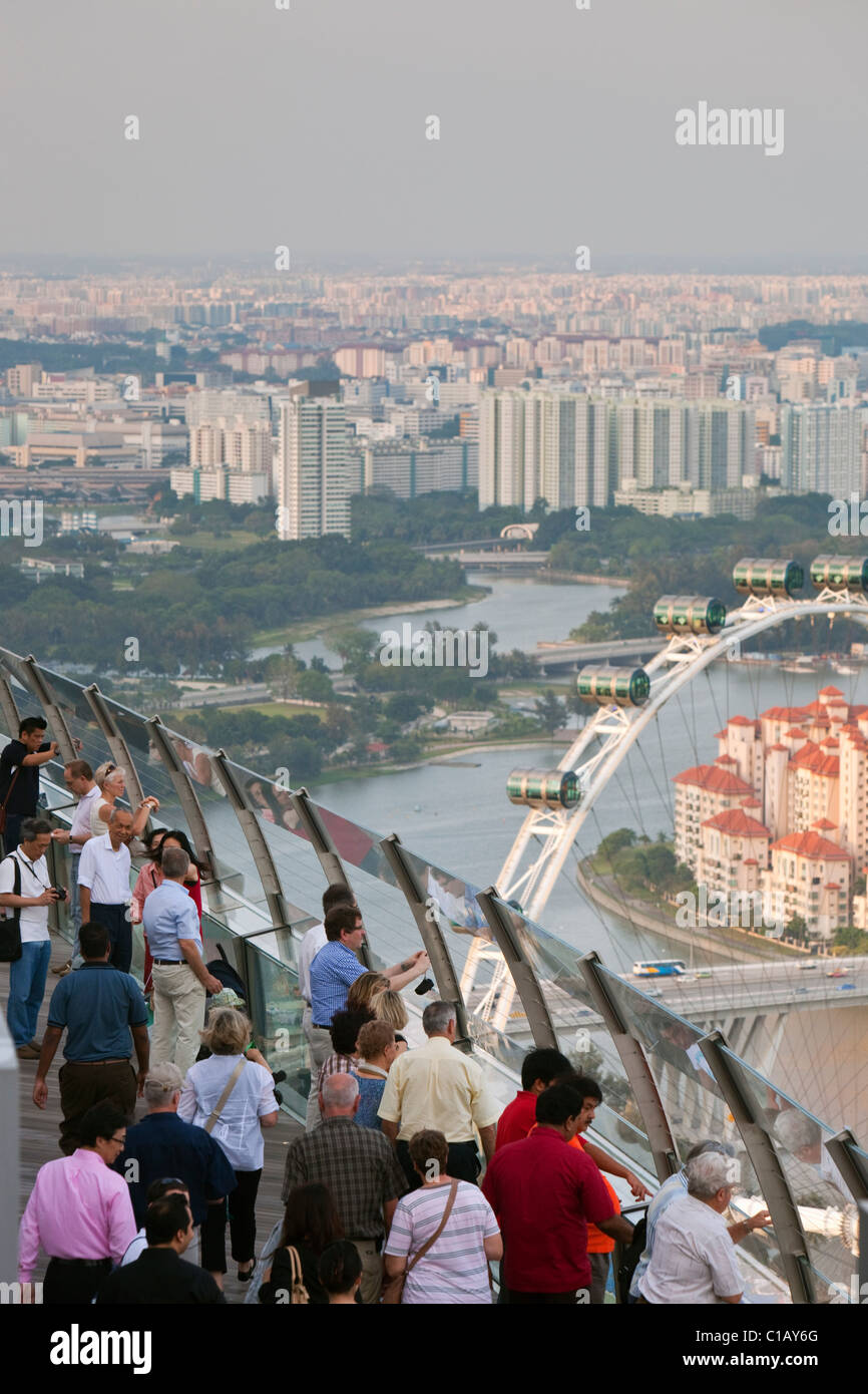 Visitors look out over the Singapore skyline from the observation deck of the Marina Bay Sands SkyPark.  Marina - Stock Image