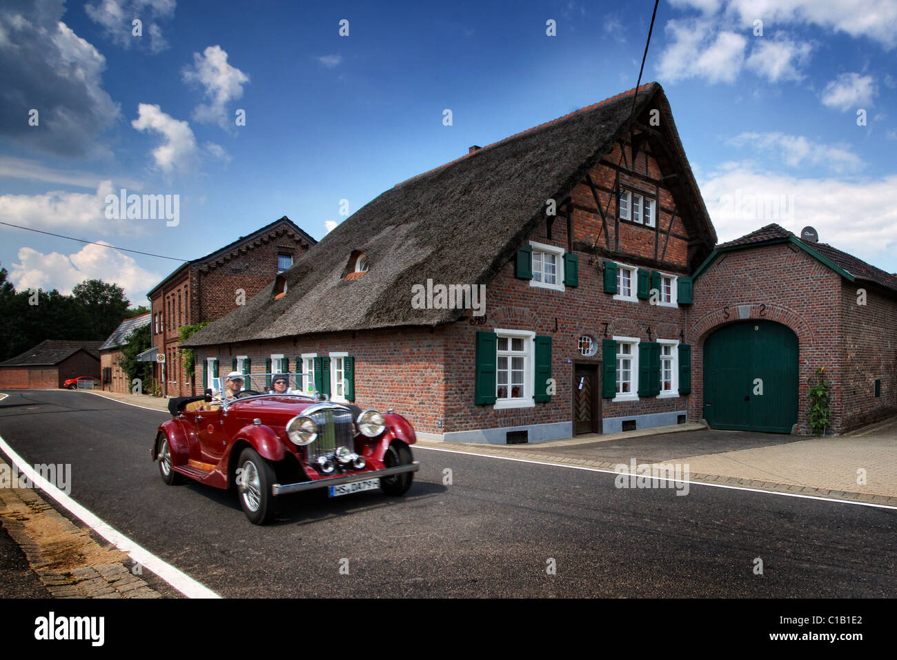27ec8c93f6 old timer race in front of old farm house in germany - Stock Image