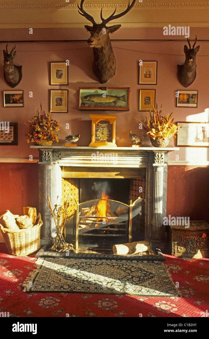Detail Of Fireplace In A Beautifully Lit Victorian Hunting Lodge Hotel With Antlers And Fishing Momentos