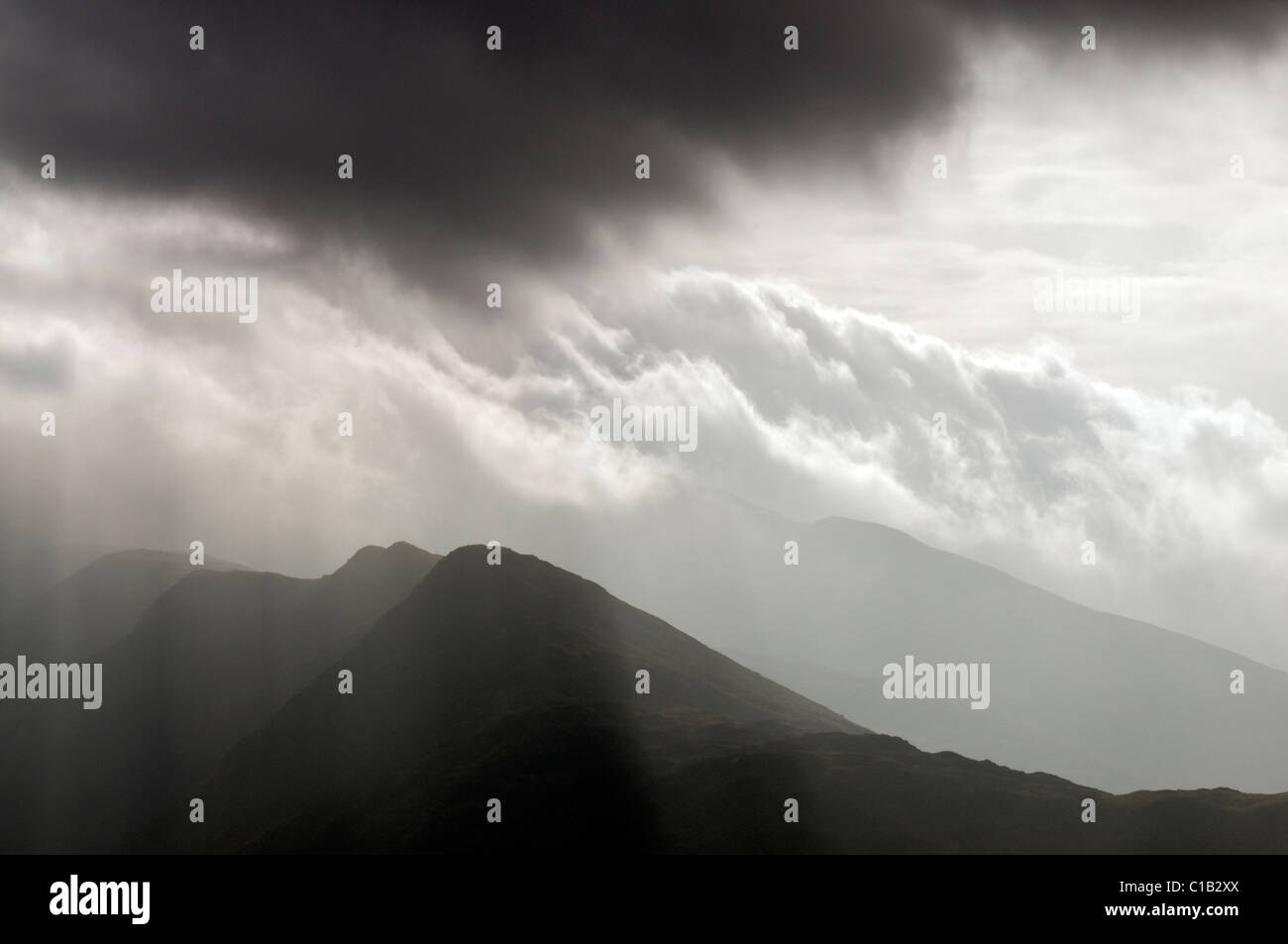 The main Llechog ridge on Snowdon, shrouded in cloud and rays of sunshine Stock Photo