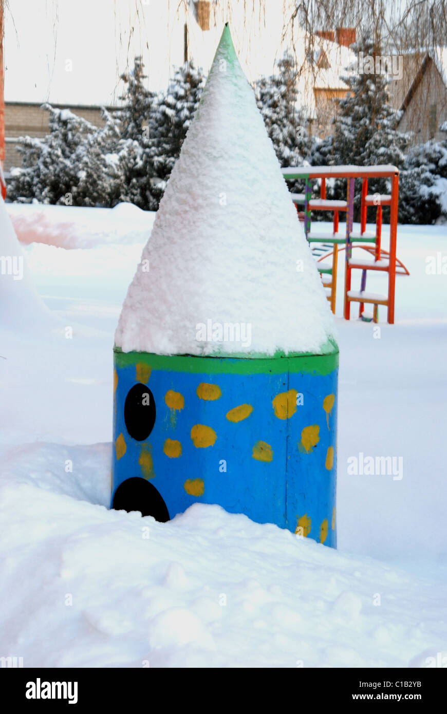 empty playground near kindergaten covered by snow in cold winter - Stock Image