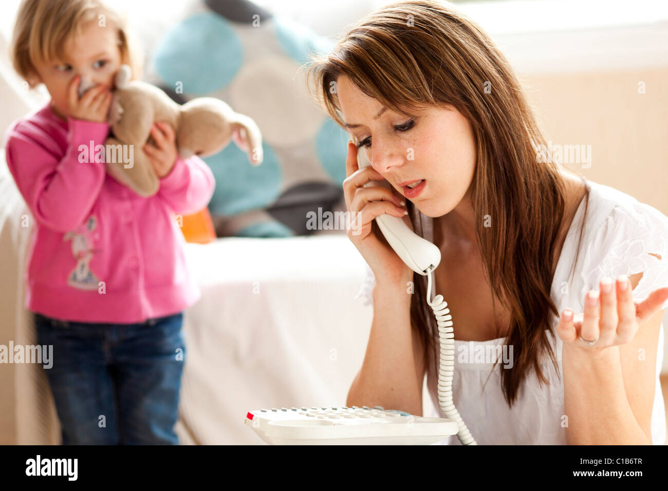 Woman on phone with child in background - Stock Image