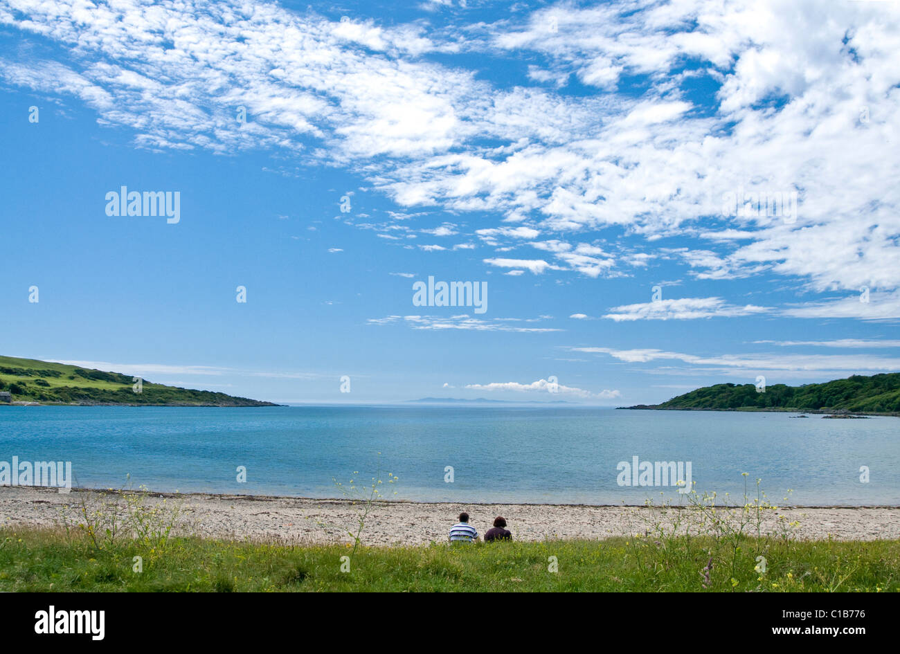 Middle aged couple meditate upon a deserted beach with big blue sky, Brighouse Bay, Galloway - Stock Image