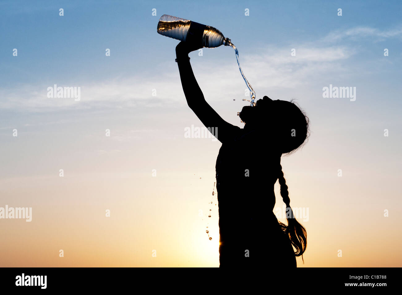 Indian girl drinking mineral water from plastic water bottle at sunset. India. Silhouette Stock Photo