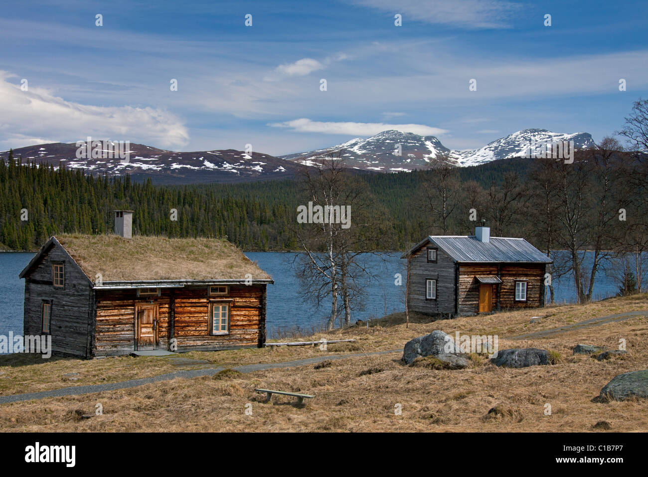Log cabin with sod roof along lake at Fatmomakke, Lapland, Sweden - Stock Image