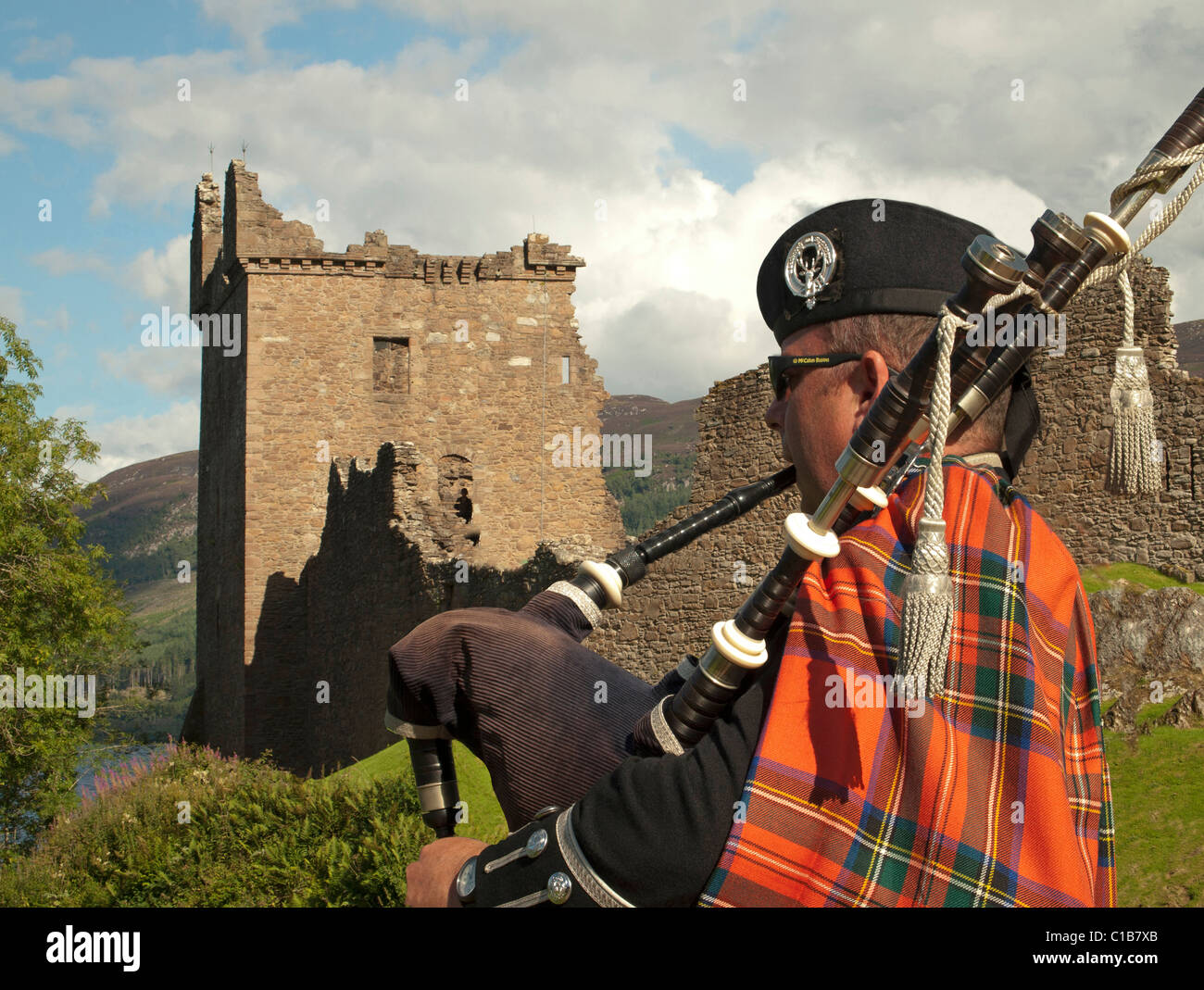 professional bagpipe player playing the bagpipes outside Urquhart Castle, Loch Ness, Scottish Highlands - Stock Image