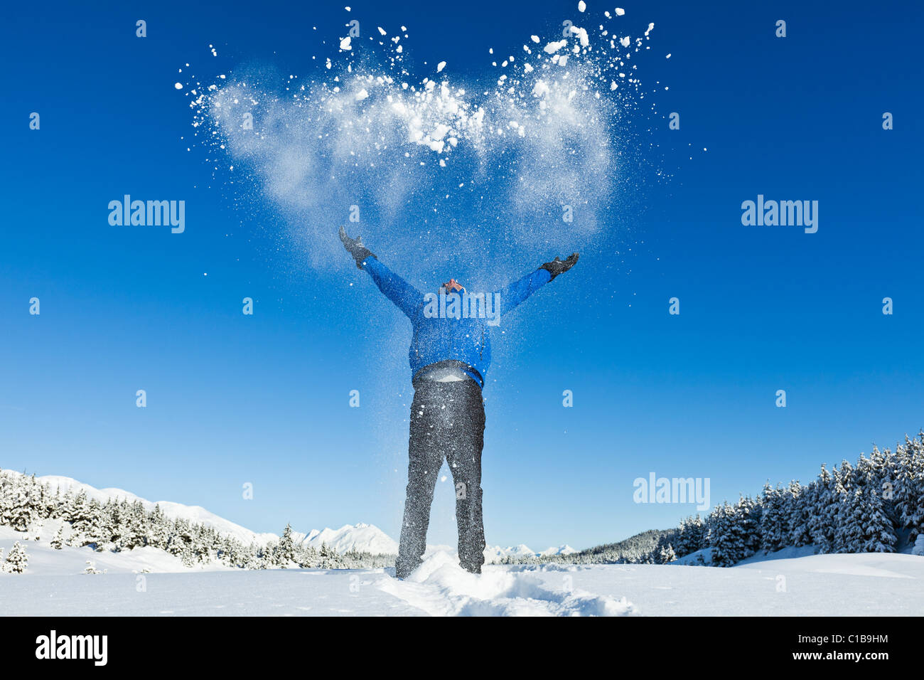 A male hiker on snowshoes in Alaska throws up snow into the air expressing joy at the sunny day and mountain scenery. Stock Photo
