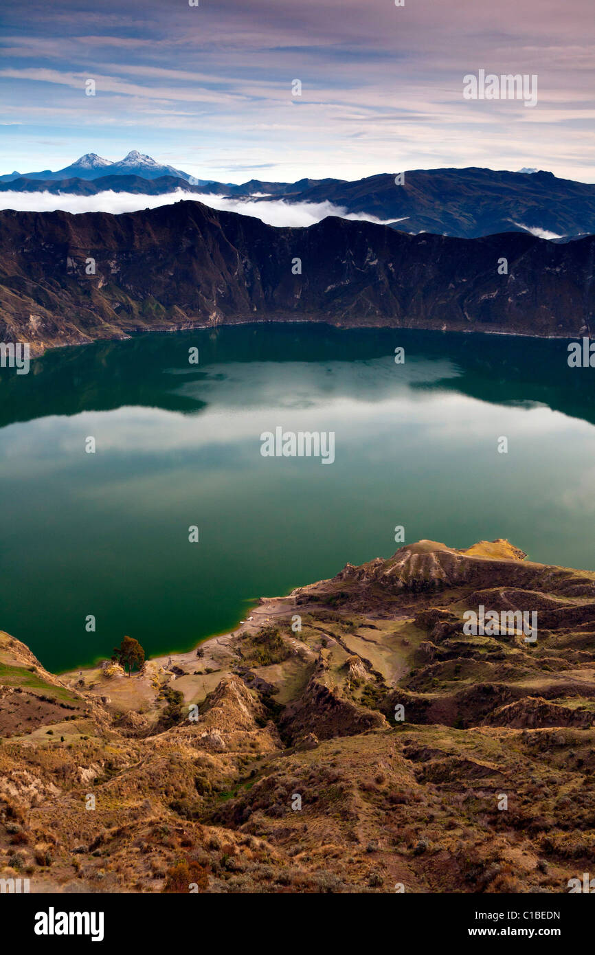 Quilotoa crater lake early morning with clear (and rare) view of Illiniza snow covered peaks (upper left), Ecuador - Stock Image
