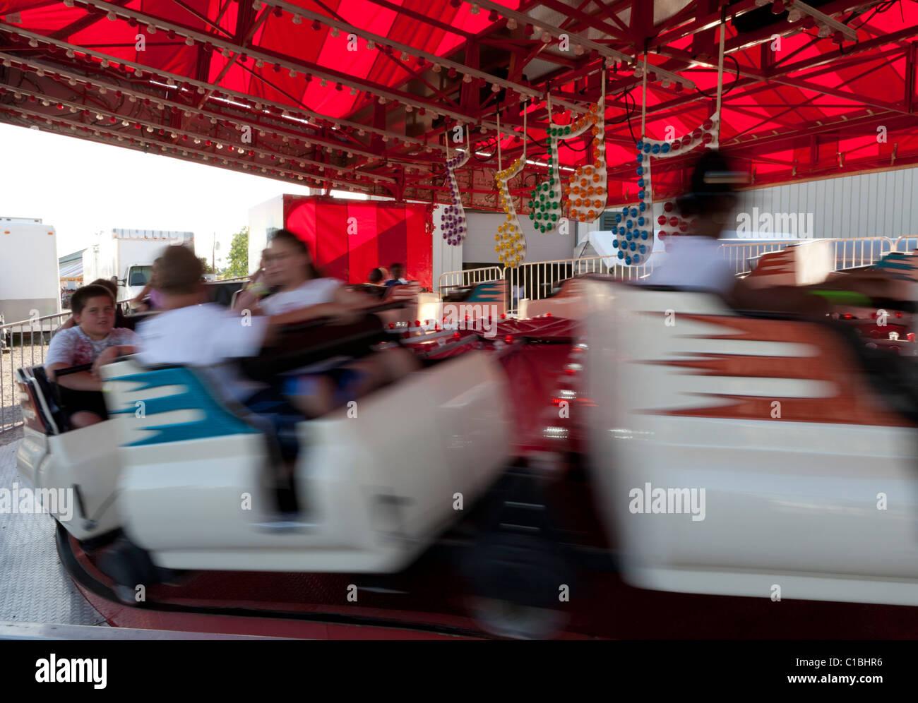 People enjoying an amusement park ride. - Stock Image