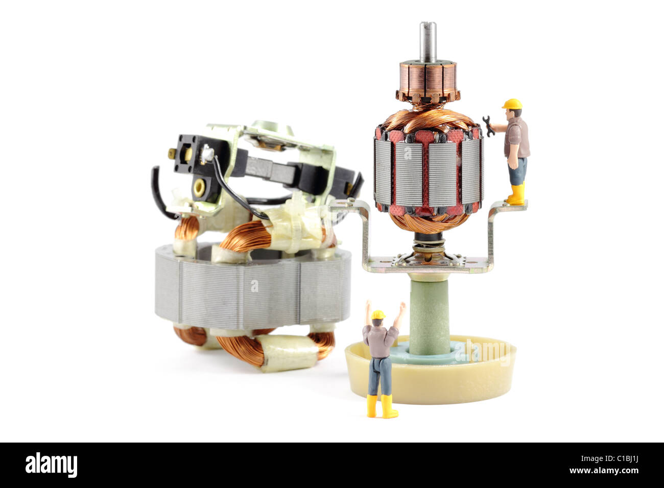 Electric Motor Repair - Macro photograph of a disassembled electric motor being worked on by two tiny toy engineers, - Stock Image