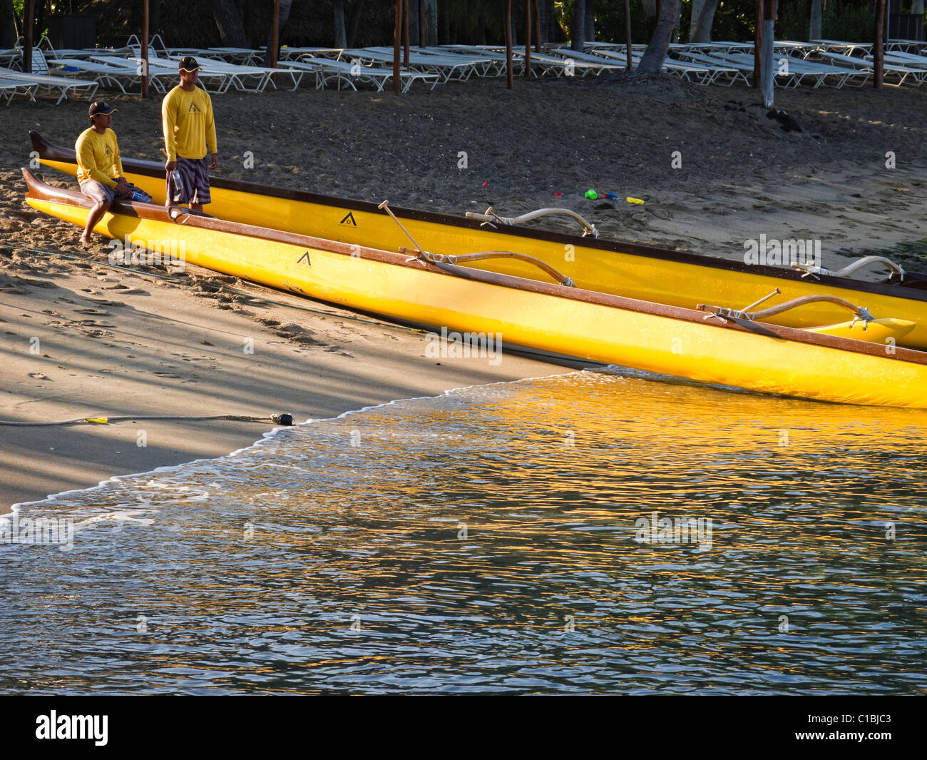Beach boys by an outrigger canoe at Kona Village in Hawaii. - Stock Image