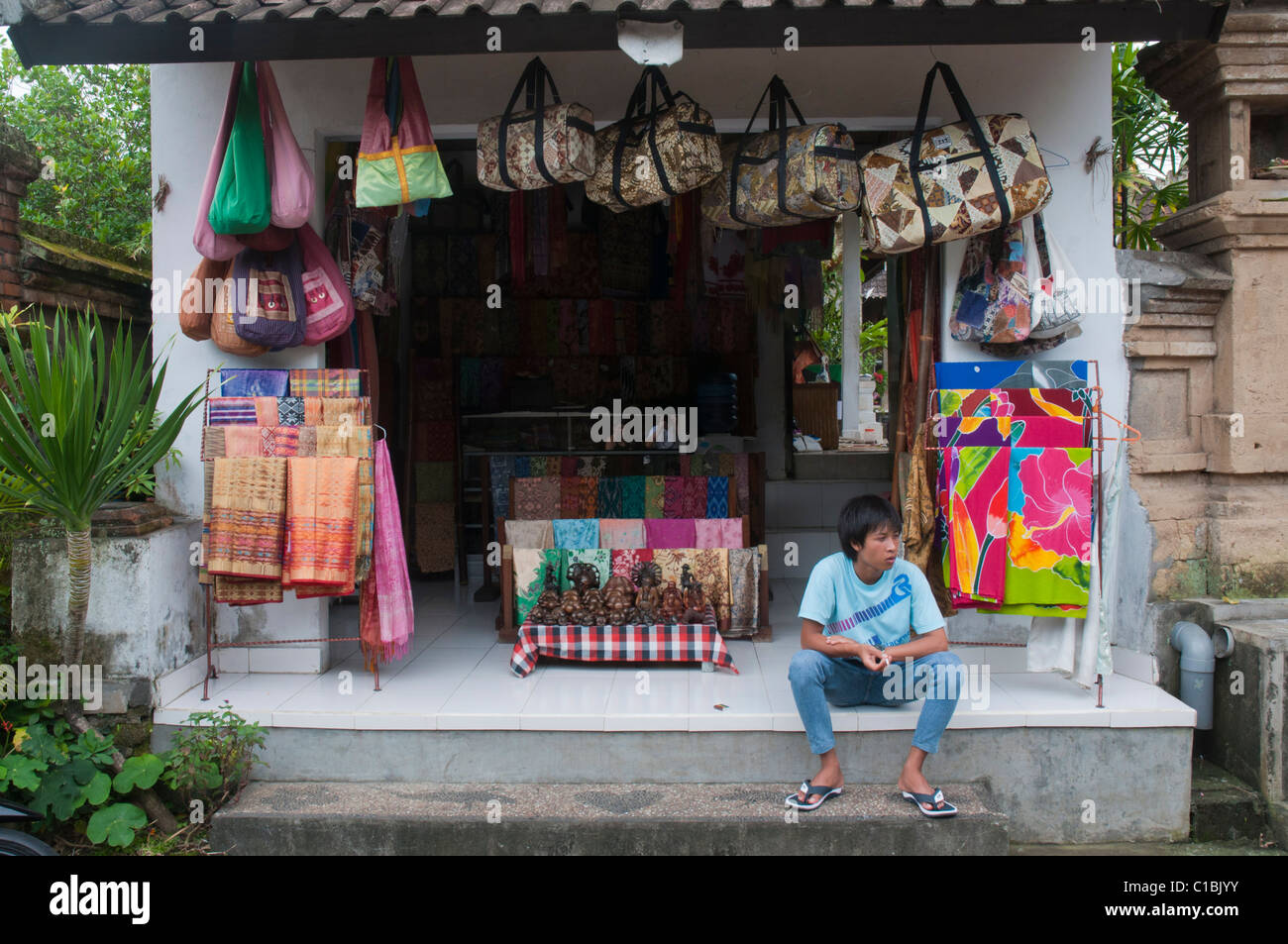 A youth sitting outside a souvenir store in Ubud, Bali Indonesia - Stock Image