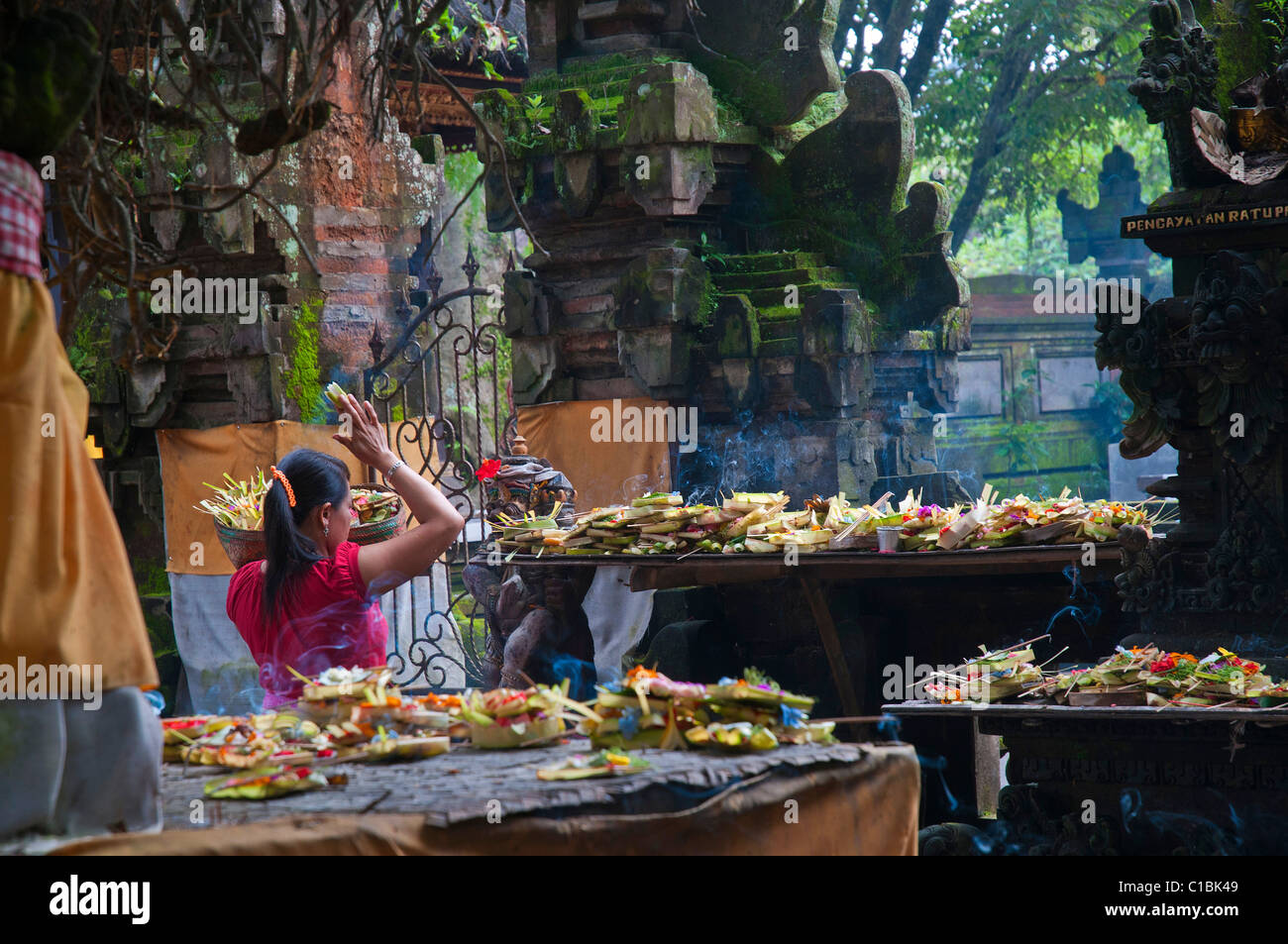 Woman making morning offerings at the busy temple near the main market in Ubud - Stock Image